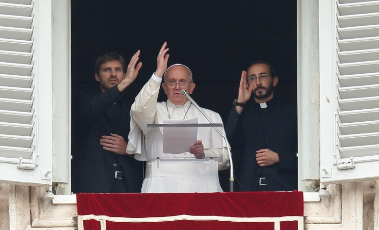 "Pope Francis and two newly ordained priests give a blessing during the ""Regina Coeli"" from the window of the pope's studio at the Vatican April 26. The priests and 17 others were ordained by the pope during a liturgy in St. Peter's Basilica that morning. (CNS/Paul Haring)"