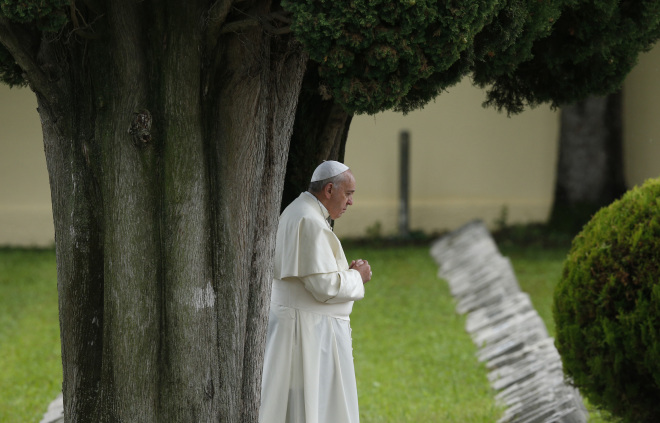"Pope Francis is shown praying at an Austro-Hungarian cemetery for fall soldiers of World War I in Fogliano di Redipuglia, northern Italy, last September. The pope in his encyclical ""Laudato Si', on Care for Our Common Home,"" released June 18, said all creation is singing God's praise but people are silencing it. (CNS/Paul Haring)"