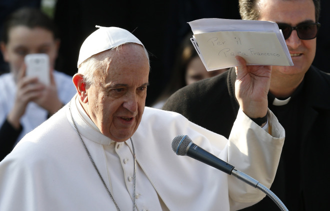 Pope Francis holds up letters he received from young people during a visit to St. Mary Mother of the Redeemer Parish on the outskirts of Rome March 8. (CNS/Paul Haring)